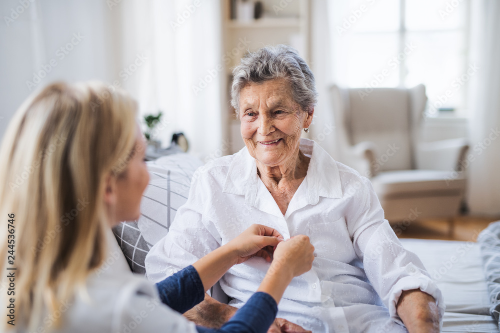 Fototapety, obrazy: A health visitor helping a sick senior woman sitting on bed at home.