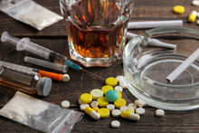 Various Addictive Drugs Including Alcohol, Cigarettes, And Drugs On A Brown Wooden Table. Drug Addiction Concept