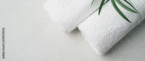 Spa concept: two white fluffy towels twisted into rolls on a light surface with Fototapete