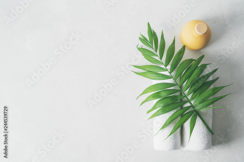 Poster Spa Spa concept: beautiful ceramic bottle, white towels and palm leaf on concrete light surface with copy space, flat lay.