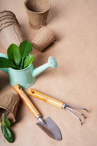 Gardening tools, paper pots, watering can on craft paper