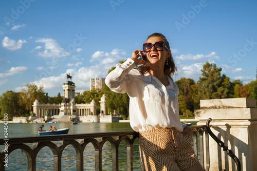 Fototapeta premium kobieta w Parque del Buen Retiro rozmawia przez telefon komórkowy