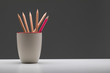 Pink pencil in cup standout from wooden pencil