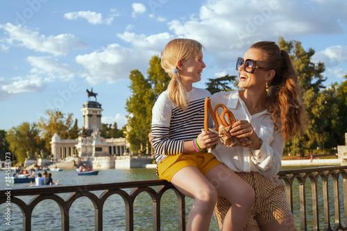 Fototapeta premium matka i córka turyści jedzący tradycyjne hiszpańskie churro