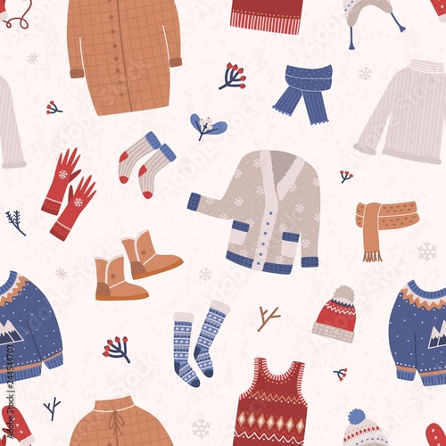 Obraz Winter seamless pattern with warm knitted clothes on light background. Backdrop with woolen seasonal clothing and accessories. Flat cartoon vector illustration for wrapping paper, fabric print. - fototapety do salonu