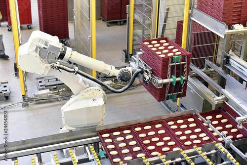 Obraz Production robot in a large bakery - Automation in the food industry // Fertigungsroboter in einer Großbäckerei - fototapety do salonu
