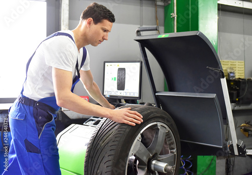 Fotografie, Tablou  tyre change in a garage - assembler balancing a tyre on the machine // Automecha