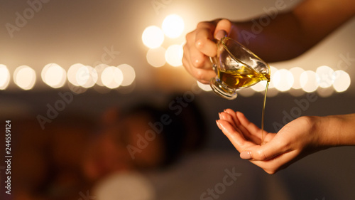 Fotografie, Obraz  Masseur pouring massage oil, woman lying on background