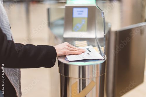 Fotografía  Electronic Boarding pass and passport control in the airport - hand with boarding pass at the turnstile