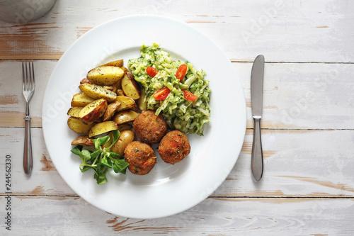 Fototapeta Pieczone klopsiki warzywne pieczonymi ziemniakami i surówka z białej kapusty . obraz