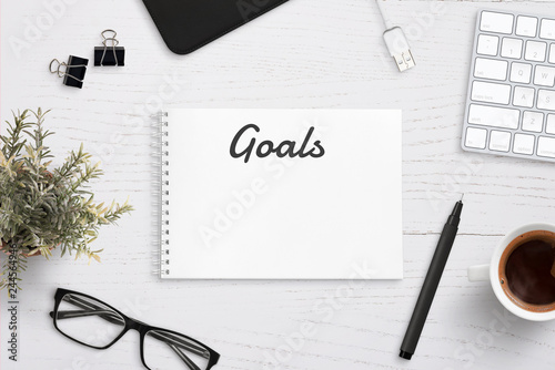 Photo  Creating goals list on notepad on office desk surrounded with office supplies