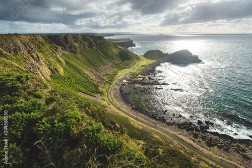 Sunlit ocean, green shore with the road. Northern Ireland landscape. Stunning lowland next to the ocean water. Panoramic overview of the untouched nature. Cloudy sky above the Irish shoreline.