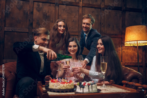 Fotografía  Cheerful friends celebrate birthday by drinking champagne and eating cake