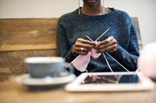 Black Woman Knitting In A Cafe