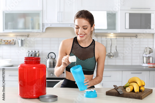 Fotografía  Young woman preparing protein shake at table in kitchen