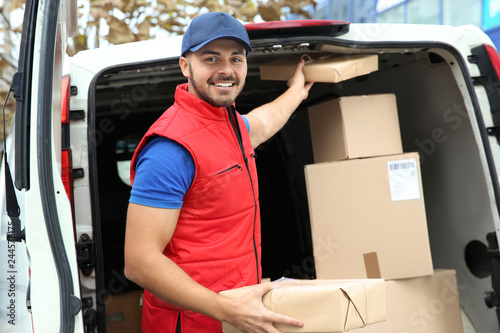 Fotografía  Young courier with parcels near delivery van outdoors