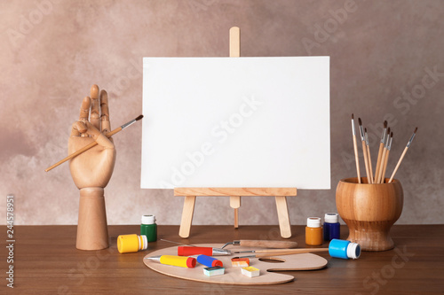 Photo  Wooden easel with blank canvas board and painting tools for children on table ne