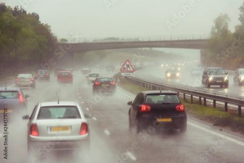 Traffics on a rainy wet highway in fog water spray #244579716