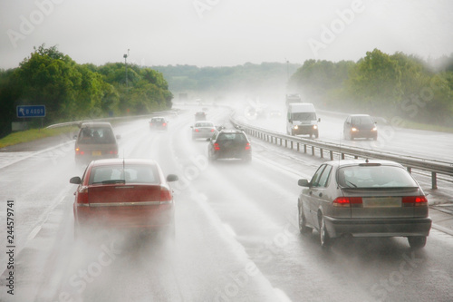 Traffics on a rainy wet highway in fog water spray #244579741