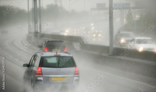 Traffics on a rainy wet highway in fog water spray #244579765