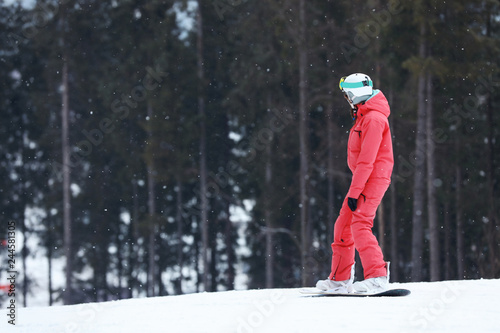 Snowboarder on slope at resort, space for text. Winter vacation