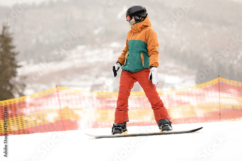 Snowboarder on slope at resort. Winter vacation