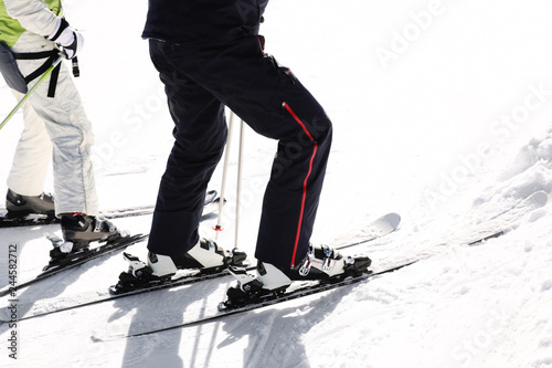People skiing on snowy hill in mountains, closeup view. Winter vacation