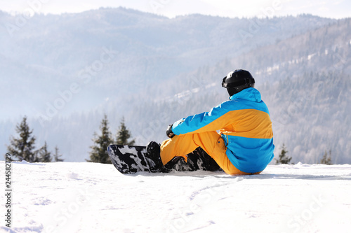 Man with snowboard resting in mountains. Winter vacation