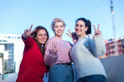 Foto  Front view of three Teenage girls making a peace sign outdoors in a sunny day