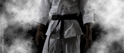 Guy poses in white kimono with black belt.  Black retouch