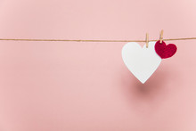 White And Red Love Hearts Pegged To A Line Against A Pastel Pink Background