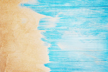 Top View Of Sandy Beach And Marine Blue Planks Pier. Background With Copy Space And Visible Sand And Wood Texture.