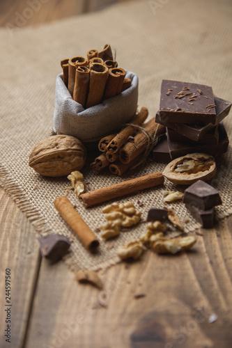 Fotografía  chocolate, canela, mesa rústica con nueces
