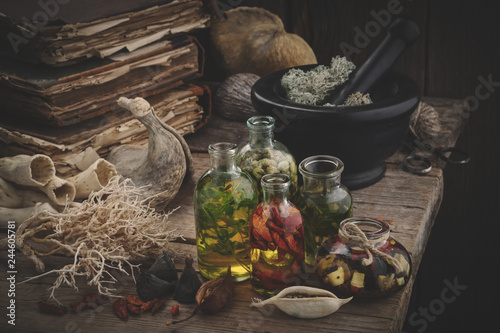 Photo  Bottles of essential oil, mortar of dried moss, old books, dry roots and plants