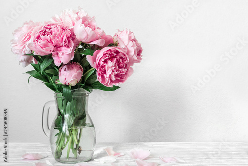 beautiful bouquet of pink peony flowers in vase. womans day or wedding background with copy space