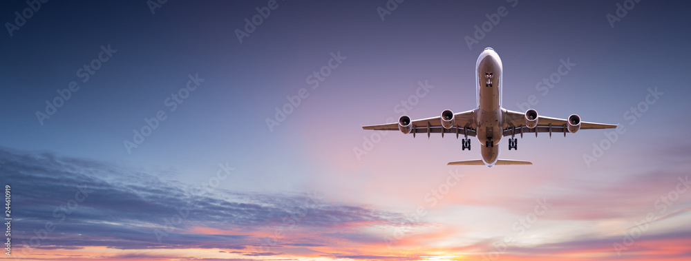 Fototapeta Commercial airplane jetliner flying above dramatic clouds.