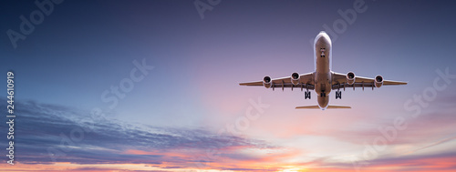 Commercial airplane jetliner flying above dramatic clouds. Wallpaper Mural