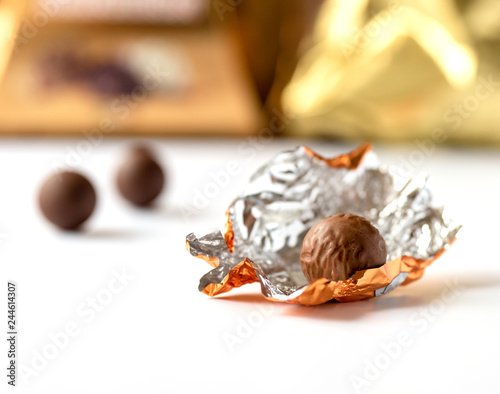 Chocolate praline wrapped in foil. Isolated on white background