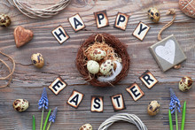 Happy Easter Lettering Text On Rustic Wood With Spring Flowers, Easter Eggs, Wooden Heart And Decorations