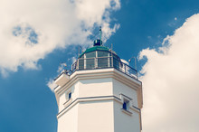 White Lighthouse Against The Blue Sky On A Sunny Day
