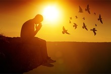 Young Man Pray Outdoor On Top Of Mountains In Sunset