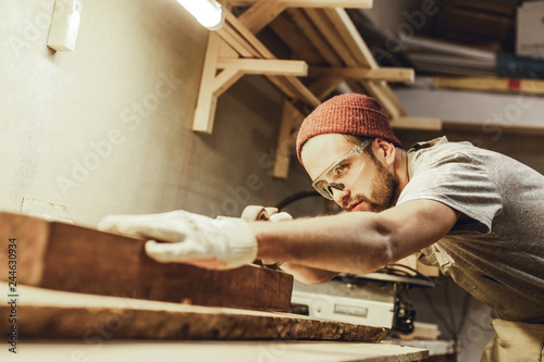 Obraz Attractive guy in protection goggles working with lumber plank on workbench in professional joinery - fototapety do salonu
