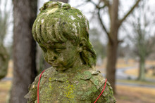 Moss Covered Statue Of A Girl Wearing A Christmas Bell Necklace, On A Grave In Greenwood Cemetery, Clarksville, Tennessee