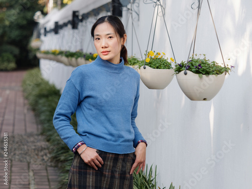 Photographie  Beautiful young brunette woman in blue sweater looking and smiling in yard