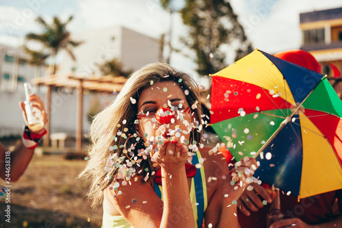 Foto op Canvas Carnaval Brazilian Carnival. Young woman in costume enjoying the carnival party blowing confetti