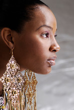 Closeup Profile Of A Beautiful Young Woman Wearing Large Golden Earrings And Looking Forward