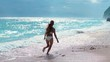 Sexy bikini body woman playful on paradise tropical beach having fun playing splashing water in freedom with open arms. Beautiful fit body girl on travel vacation.