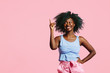 canvas print picture Portrait of a cool, happy young woman with blue curly hair pointing up and looking up, isolated on pink background