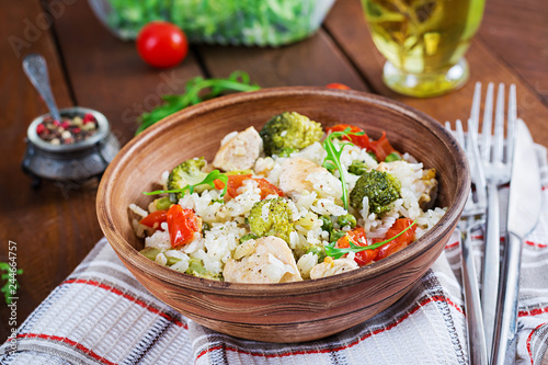 Delicious chicken, broccoli, green peas, tomato stir fry with rice. Asian cuisine. Healthy food.