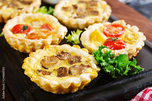 Mushrooms, cheddar, tomatoes tartlets on wooden background. Mini pies. Delicious appetizer, tapas, snack.